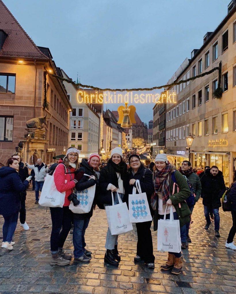 Women standing in front of Christmas market in Nuremberg.