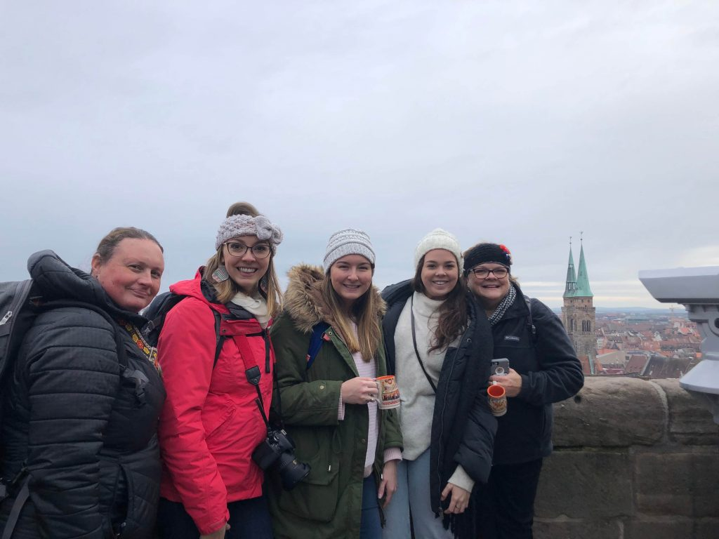 Women standing in front of balcony smiling at camera. Nuremberg church in background.