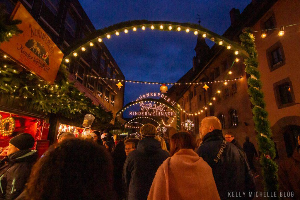 People walking under lights at the Christmas market in Nuremberg.