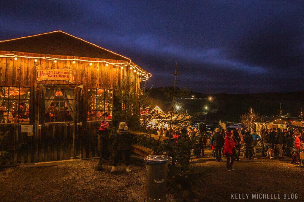 People walking through Christmas Market (Schloss Guteneck) at night.