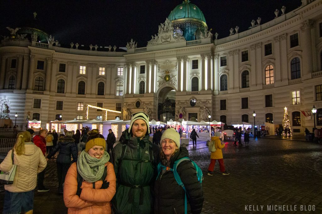 Two women and a man standing in front of Hofburg Palace at night in winter.