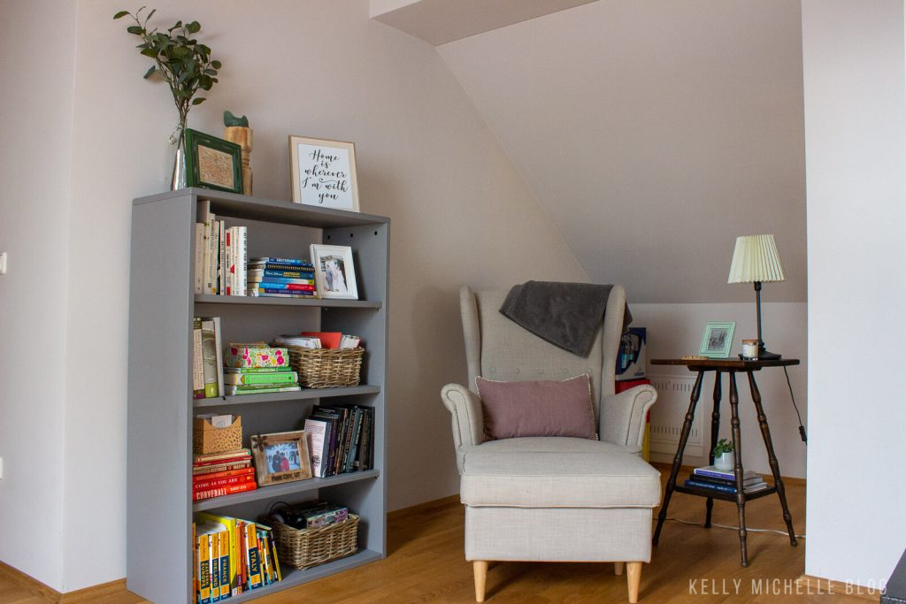 Gray bookshelf with books on it. Gray chair with purple pillow and a side table with a lamp and picture frame.