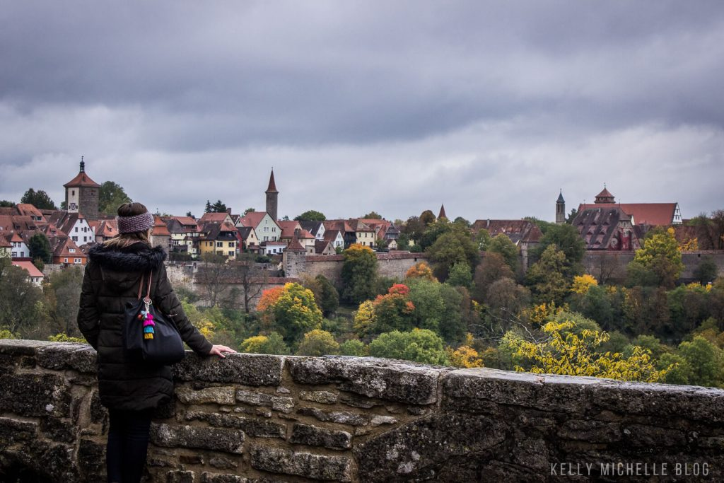 Woman standing and overlooking a valley of trees and German buildings.